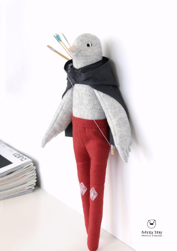 - Soren est une poupée décorative, un archer tribale fait de coton. Il porte une cape grise en coton et un pantalon rouge brique en coton. Il porte également un arc en bambou et trois flèches au plumeau bleu cyan en bambou et en papier. Il tient debout grâce à son présentoir / socle en bois offert avec la poupée, Il est prête à exposer. (Conférer la dernière photo)(via Poupée décorative / objet décoratif / oiseau archer par PopetseToys)