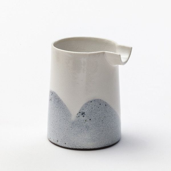 Pitcher in ceramic - perfect for milk or cream for coffee and tea. Can also be used for the dressing to the salad. The pitcher is 10 cm high and has a diameter of 6,5 cm at the top. It can hold 2,5 dl. The colour can vary from a light to a darker shade on the blue arches.