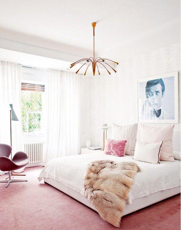 Blush tones, pink carpet, and faux fur throw in this feminine bedroom