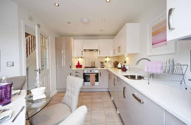 Interior Designed very small kitchen dining room, using pale dove grey gloss units mixed with white - I love the touch of colour introduced by the painting above the sink. Taylor Wimpey 2015