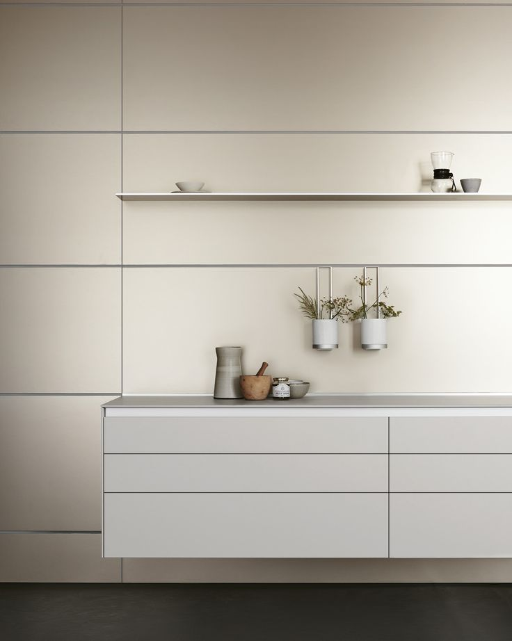 In combination, the gravel-grey laminate suspended wall unit and sand-beige aluminum panels create a warm and inviting kitchen atmosphere.