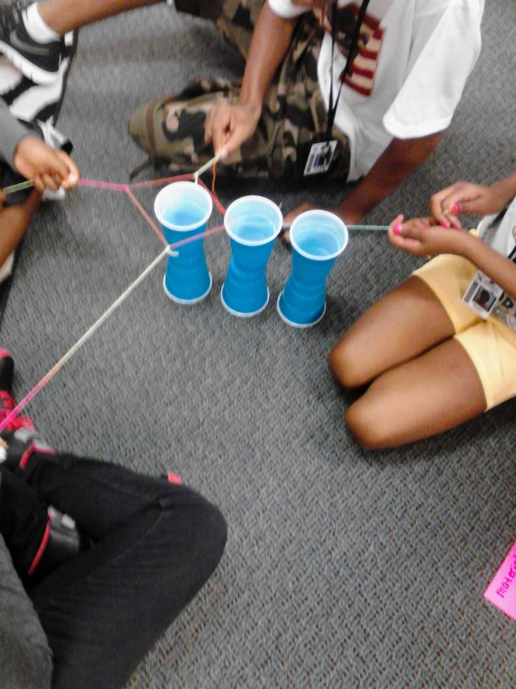 Given 6 cups, 4 - 7 strings, and 1 rubberband, move the cups from the starting position to a pyramid without any person touching the cups.