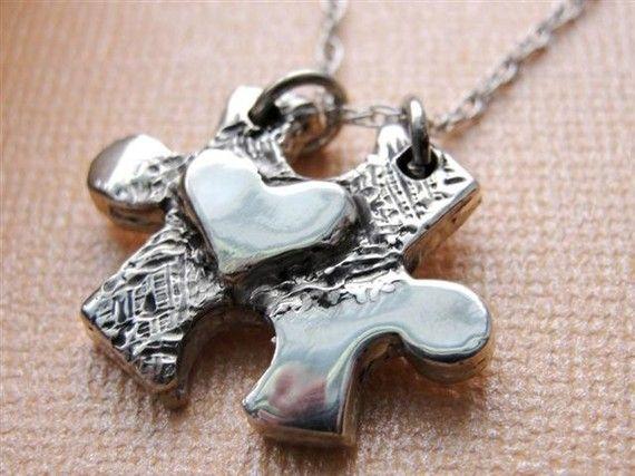 een verzilverd puzzelstukje  met een hartje erop als ketting-hanger  piece heart necklace.