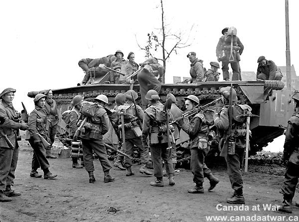 The Netherlands - Infantrymen of the North Shore Regiment boarding an Alligator amphibious vehicle during Operation Vertiable near Nijmegen, Netherlands, 8 February 1945.