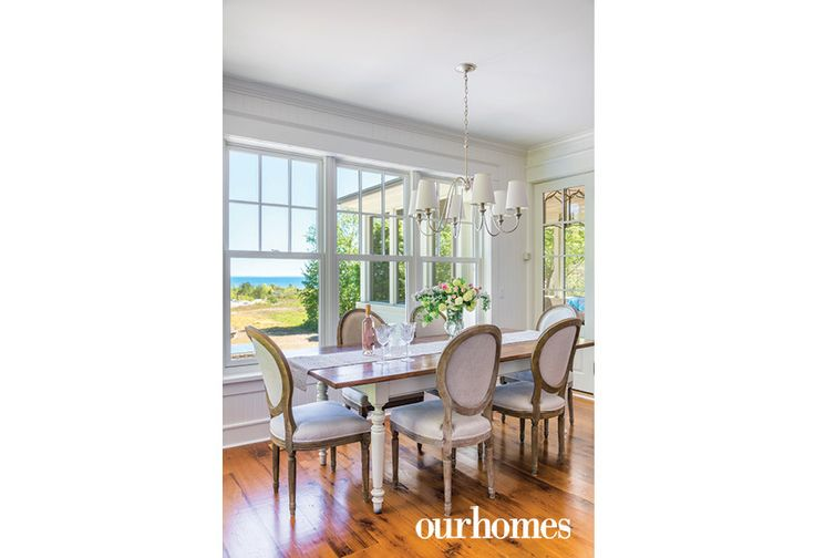 "A bank of windows in the dining room can easily distract from the evening meal. One door leads to the screened porch, the other accesses the outdoor deck.    See more of this home in ""Cape Cod Style Home on the Shores of Georgian Bay"" from OUR HOMES Southern Georgian Bay, Summer 2017 http://www.ourhomes.ca/articles/build/article/cape-cod-style-home-on-the-shores-of-georgian-bay"