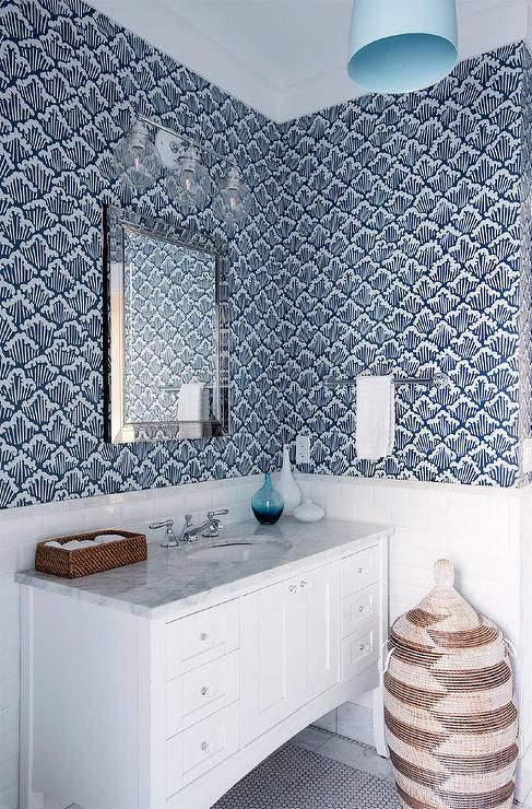 Clad in Farrow & Ball Aranami Wallpaper, this blue beach style bathroom features an African woven hamper with a lid placed in front of a white washstand accented with white legs and a carrera marble countertop fitted with an oval sink and polished nickel faucet placed in front of white subway backsplash tiles and under a beveled vanity mirror lit by a 3 light glass globe sconce and a turquoise blue dome pendant.
