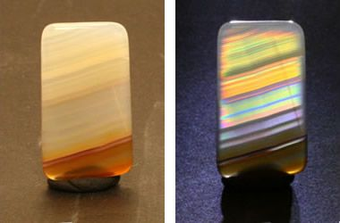 "Two views of a specimen of iris agate. The photo on the left was taken in normal light and displays the color of light reflected from the agate. The photo on the right shows the agate with backlighting. The backlighting reveals the diffraction grating or ""iris"" effect produced when light passes through the very fine banding of the agate. This specimen is a thin slice of Brazilian agate that measures about 25 mm high, 14 mm wide and 3 mm in thickness."