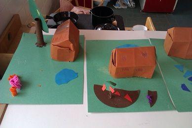 de kinderen vouwen een 3d huisje en maken er een mooie tuin bij.