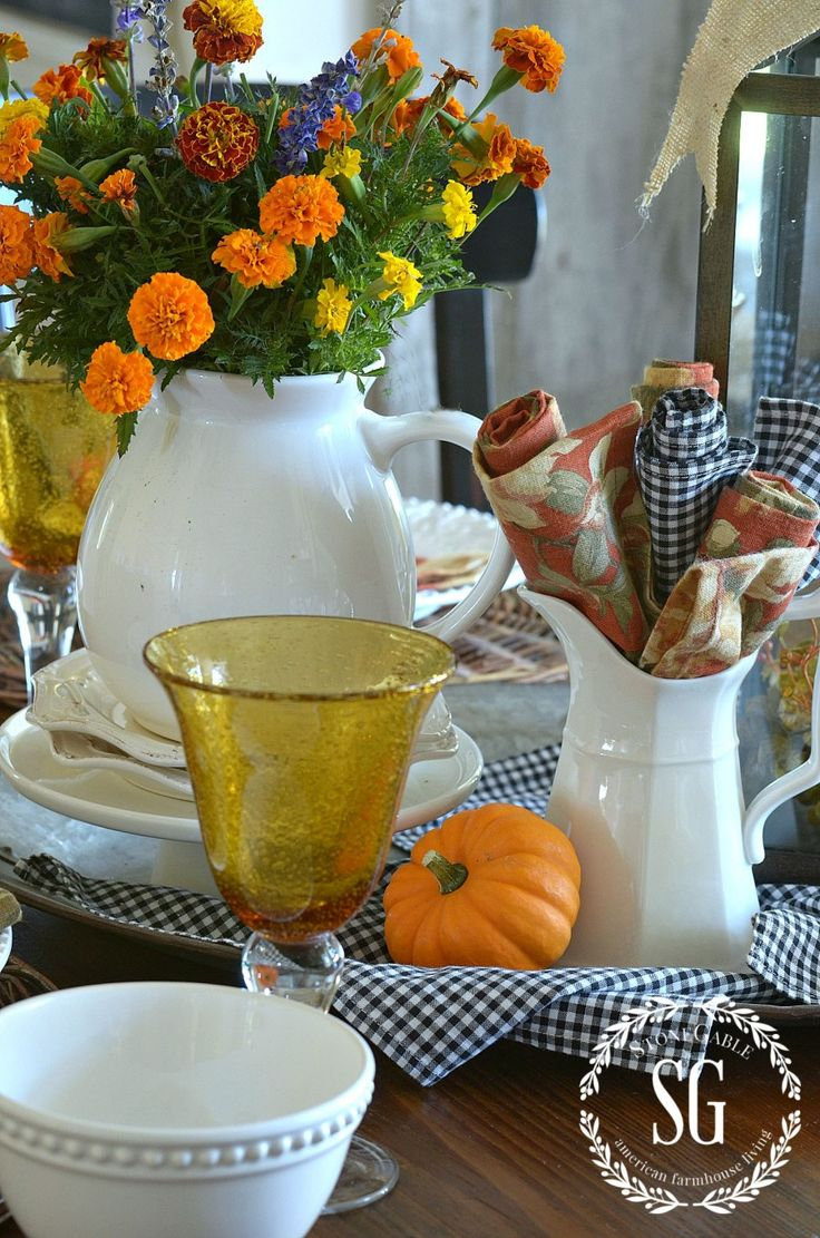 The breakfast room is complete with blue-and-white checkered cloth napkins, a pumpkin on each plate, and a pitcher filled with cheery mums. See the full home tour at Stone Gable »   - GoodHousekeeping.com