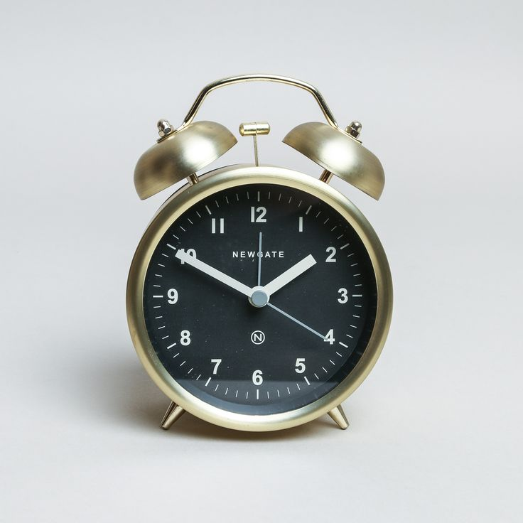Newgate Clocks Brass Charlie Bell Alarm Clock: A contemporary twist on the traditional twin bell alarm clock in a brass finish, from British brand Newgate Clocks, with a modern graphic grey dial, glass lens, metal hands and a moving hammer with a real bell alarm. Also available in matt black with a white dial.