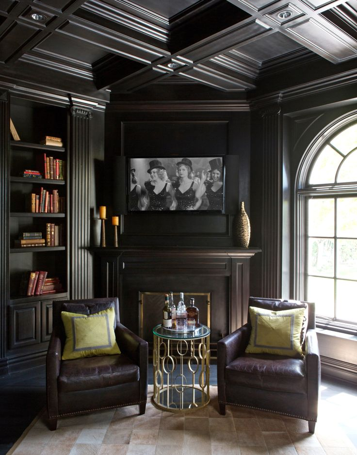 The home office's dark wood panelling and decor give the room a clubby feel | archdigest.com