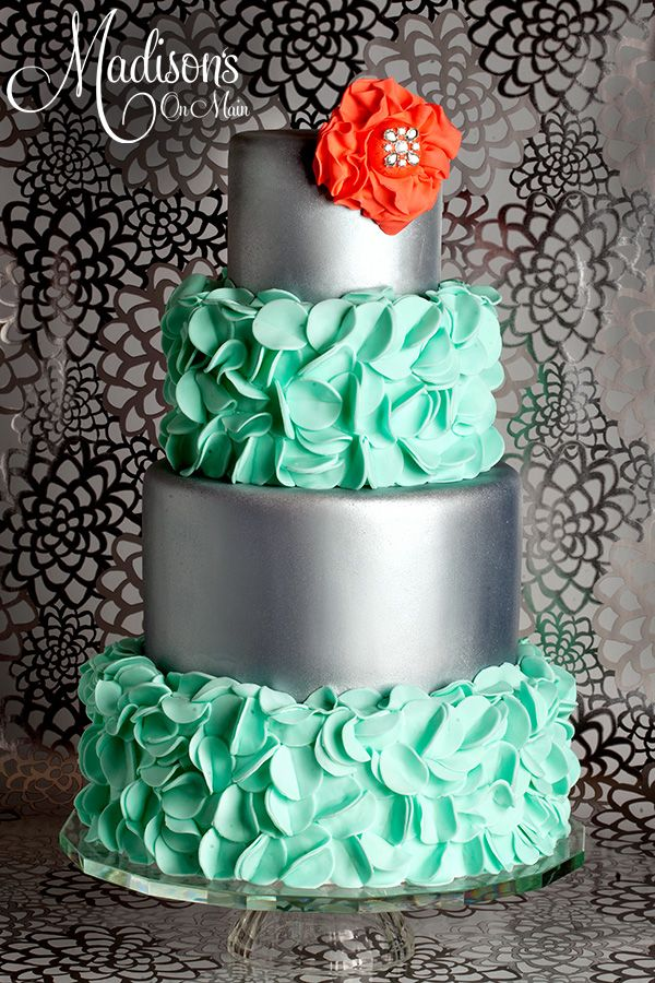 Turquoise petals and silver - I was asked to create a cake for a local bridal magazine.  They wanted something soft and hard.  So I started with two tiers that I covered in gray fondant.  I used Chefmaster silver spray to achieve the metallic finish.  I did about three coats on each tier.  Then I hand cut turquoise fondant circles and folded them in half to create the petals.  I made the flower out of coral fondant, with a rhinestone center.