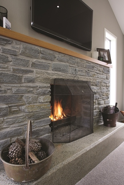 A cosy stone fireplace warms the lounge in this Southland farmstead.