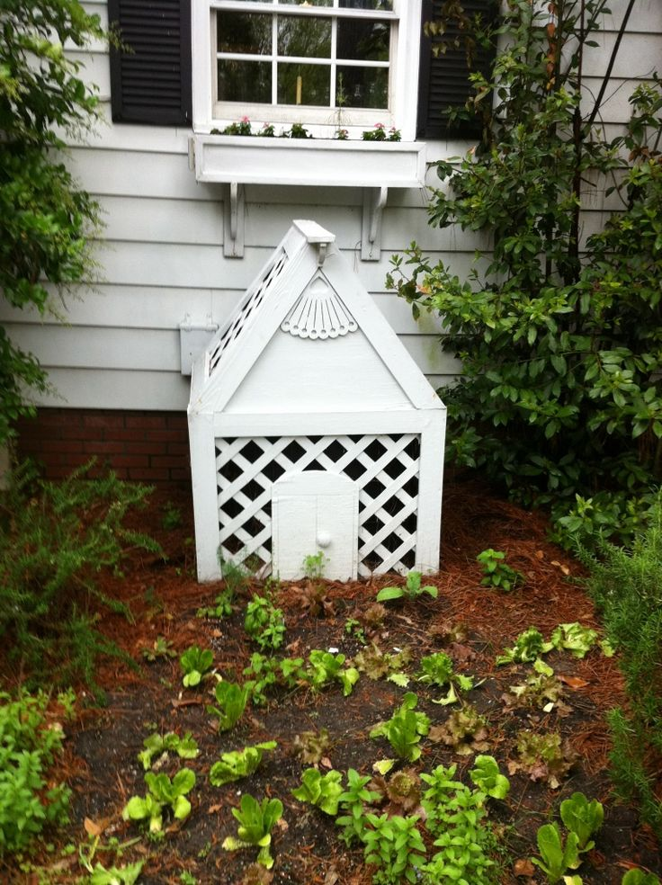 This little miniature cottage hides an AC unit! It is lightweight—easily picks up for service; but you can't tell the unit is within it. A simple box made from 1×3′s, lattice, and cute wood finials and decorative cutouts from the home store. This would be an easy 1/2 day job—including the painting! The latticework lets in air circulation
