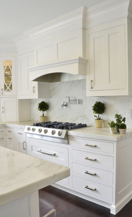 Beautiful kitchen with white ceiling height cabinetry pairing with contemporary nickel hardware alongside white Imperial Danby Marble countertops and a seamless marble backsplash.