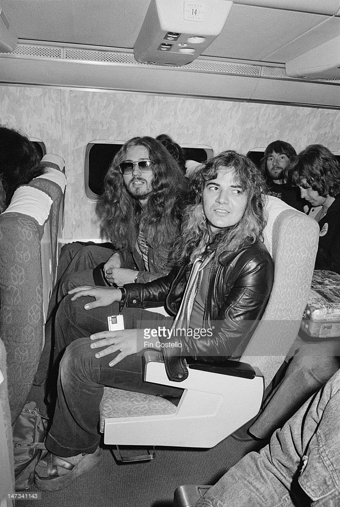 David Coverdale, singer with English rock group Deep Purple sits in an airline seat beside guitarist Tommy Bolin on an internal flight during their tour of Japan in December 1975.