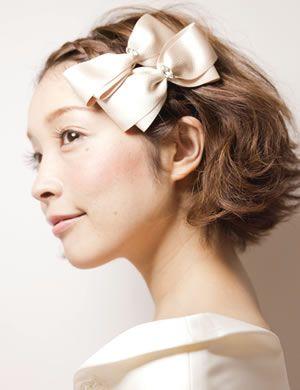 前髪を編み込んだ、キュートな髪型。連なったホワイトのリボンがさらに花嫁の可愛らしさを引き立てます。