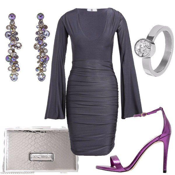 Outfit composto da vestito grigio con maniche lunghe e ampi tagli, sandali minimal color viola, clutch grigio argento, orecchini importanti e anello con pietra.
