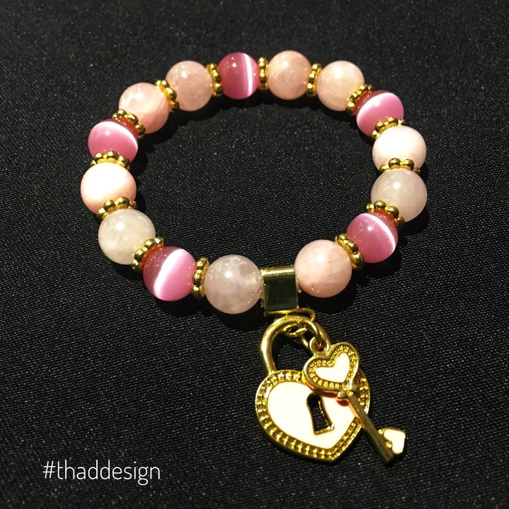 Rose quartz stone and cats eye pink glass with a pink and gold colour heart lock and key pendant... how much do you love this piece?  #bracelet #love #thaddesign