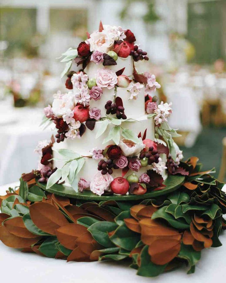 Fruit-covered wedding cake wreathed with magnolia leaves
