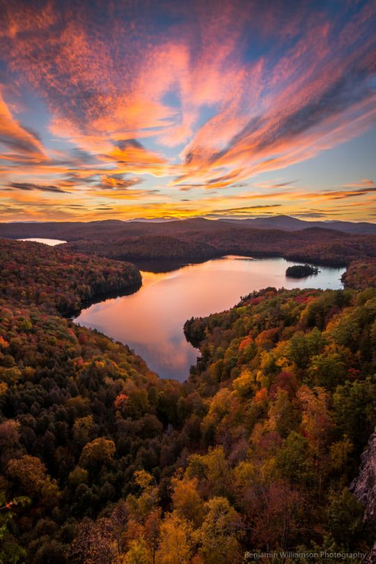 Sunset over Nichols Pond  A stunning sunset over a idyllic pond in Northern Vermont surrounded by vibrant fall foliage covered hills.