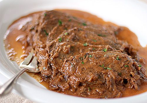 Sauerbraten ~ serves 10-12 5 lbs. top or bottom round beef roast 4 tablespoons canola oil 4 large yellow onions, thinly sliced 5 cloves garlic, minced 3 bay leaves 5 tablespoons tomato paste 1/3 cup ketchup 1 cup red wine vinegar 2 cups red wine, a good Burgundy is nice 1/2- 1 cup water Kosher salt and freshly ground pepper to taste 1/3 cup sour cream