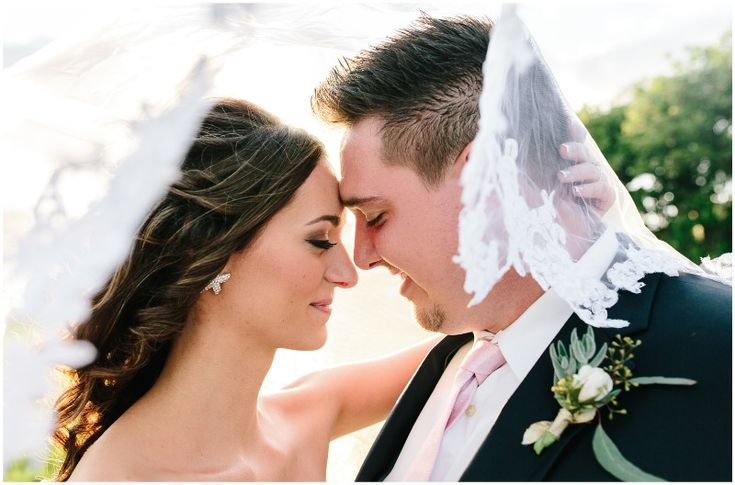 Under the veil shot with these gorgeous newlyweds! Venue: Paradise Cove - Orlando, FL Photography: Lizzie Randazzo Photography