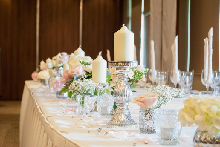 Top table, votives, candles and flowers by Laurel Weddings
