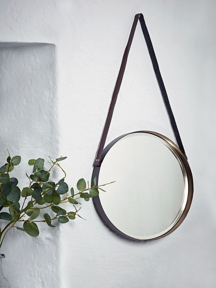 £70 Reminiscent of an old-fashioned port hole, our round metal mirror has a dark brown exterior and metallic gold interior that reflects in the mirror. Suspended from a quality faux leather strap that wraps around each mirror, this simple and stylish mirror is perfect in your hallway, kitchen or living space.
