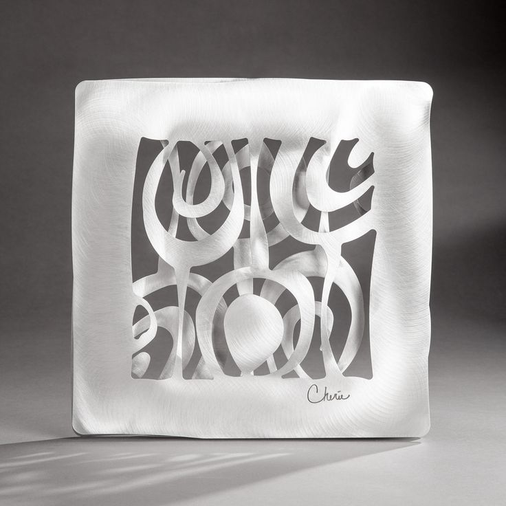 Onion Flower by Cherie Haney. Inspired by Mid-Century Modern design.Two layers of intricately cut pattern juxtapose with each other as the layers hover but do not touch adding a 3-D quality that occupies true space. Made from dramatically brushed aluminum that is powder coated with a durable clear that holds up indoor or out . Hanging hardware for drywall included. Dimensions: 14″H, 14″W, 1.5″D
