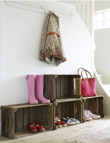 Une solution rangement pour les chaussures dans l'entrée de la maison réalisée avec des caisses en bois simplement posées au sol
