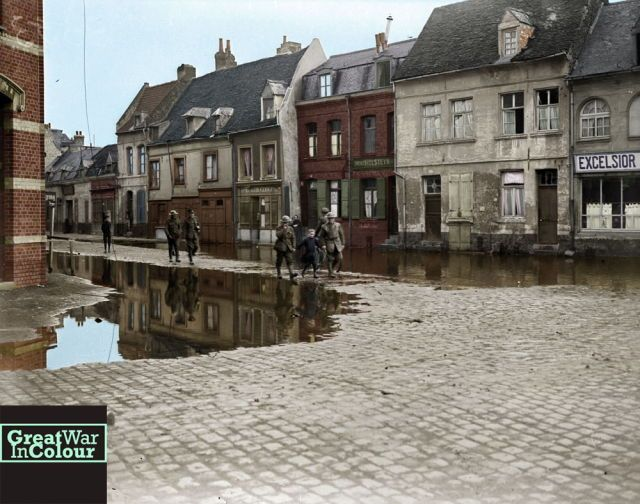 A young girl leads Canadian soldiers down Rue de Rempart in Valenciennes, France in November, 1918.