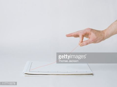 Stock Photo : Hand elevating graph line off the page