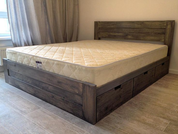 Двуспальная кровать из тонированного массива сосны с вместительными ящиками для хранения вещей.