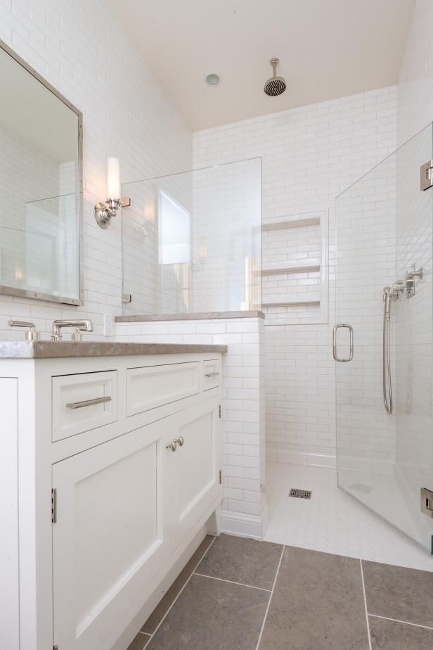 This HGTV  bathroom style becomes more streamlined and contemporary with tile walls, shelving built into the shower and a glass shower door.