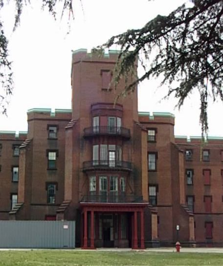 A color image of the oldest building at St. Elizabeth's Hospital - a multi-story building with 3 balconies on the floors over the entrance a...