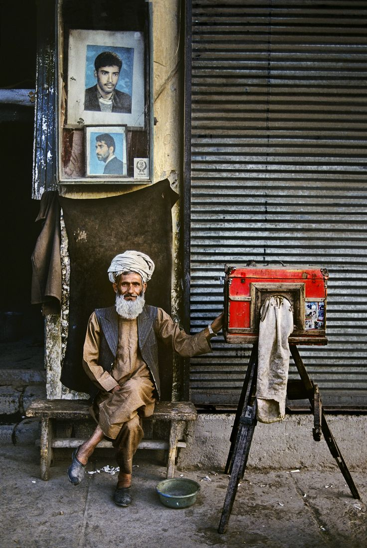 ortrait photographer, Kabul, Afghanistan.  A small but industrious group of photographers have worked the streets of Kabul for decades. Using simple box cameras, they have captured husbands going to war and sons about to come of age or be married. In McCurry's portrait, the man's studio is actually the cubicle in which he sits. After the picture is taken, the negative is developed in the small bowl at his feet.