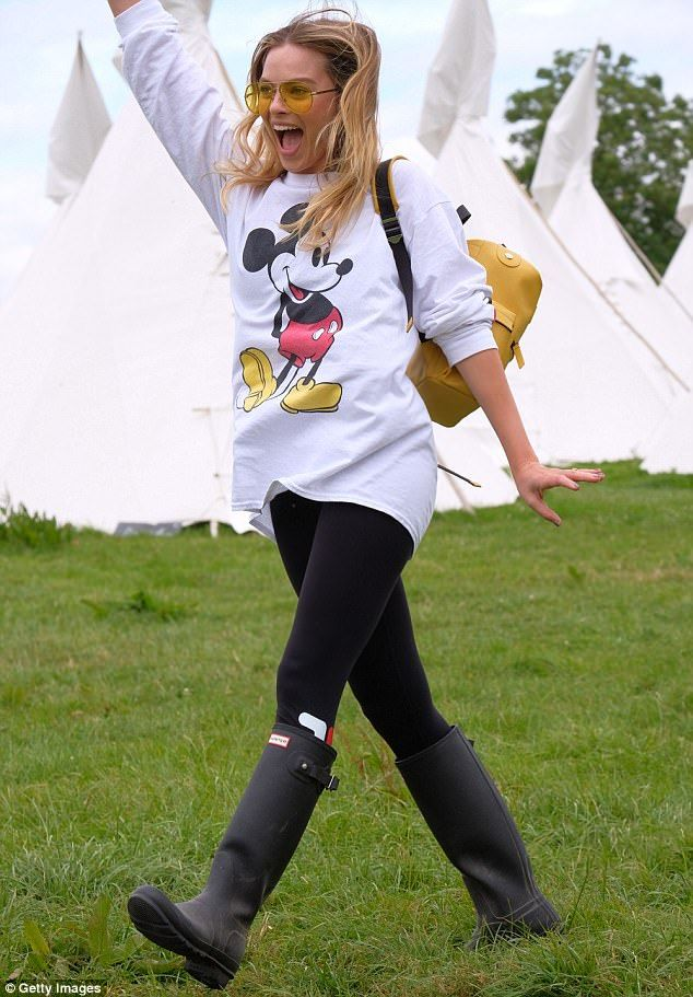Margot and the music! Margot Robbie wore a Mickey Mouse jumper and yellow shades as she joined supermodel Cara Delevingne for another day at Glastonbury Festival in England