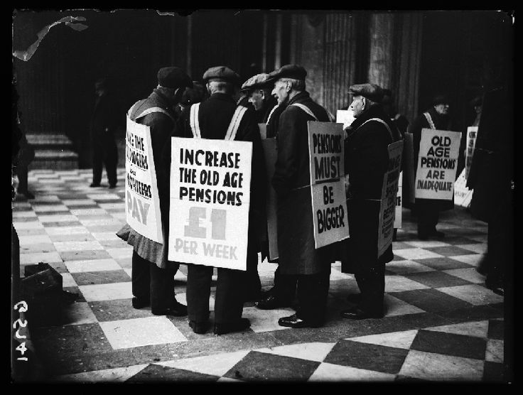 A photograph entitled 'Pensioners protest', taken in November 1938 by George W Roper for the Daily Herald.    The men stand in the porch of St Paul's Cathedral, London, wearing sandwich boards demanding a £1 a week increase in pensions. The 1908 Old Age Pensions Act introduced the first old age pension on a means tested basis. State pension for all was introduced with the 1946 National Insurance Act.