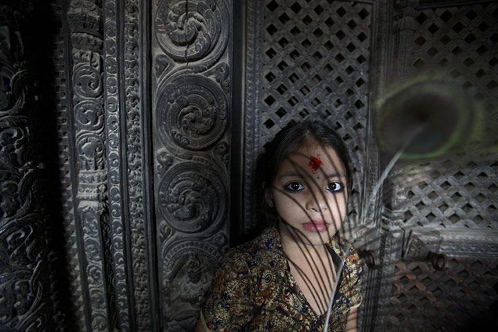 Lalitpur, Nepal: A girl holds a peacock feather during the Krishna Janmashtami festival, which marks the birth of the Hindu god Krishna