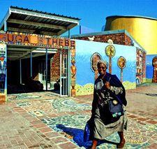 """Carin Smuts, architecte afrikaner travaillant essentiellement dans les townships du Cap. Elle utilise des matériaux peu chers (briques et tôles ondulées), dans le but d'un habitat durable — c'est-à-dire qui ne sera pas démantelé par les gangs pour récupérer les matériaux! Elle implique les habitants dans ses projets architecturaux, dans leur conception et leur réalisation. Dans un pays où les plans d'urbanisme sont quasi inexistants, """"c'est à l'architecte de remplacer l'action publique""""…"""