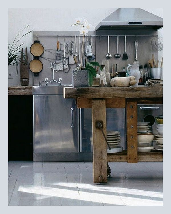 Love the old wooden workbench used as a kitchen island in this
