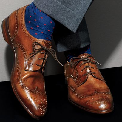 Bright blue socks complement the beautiful brown shoes.