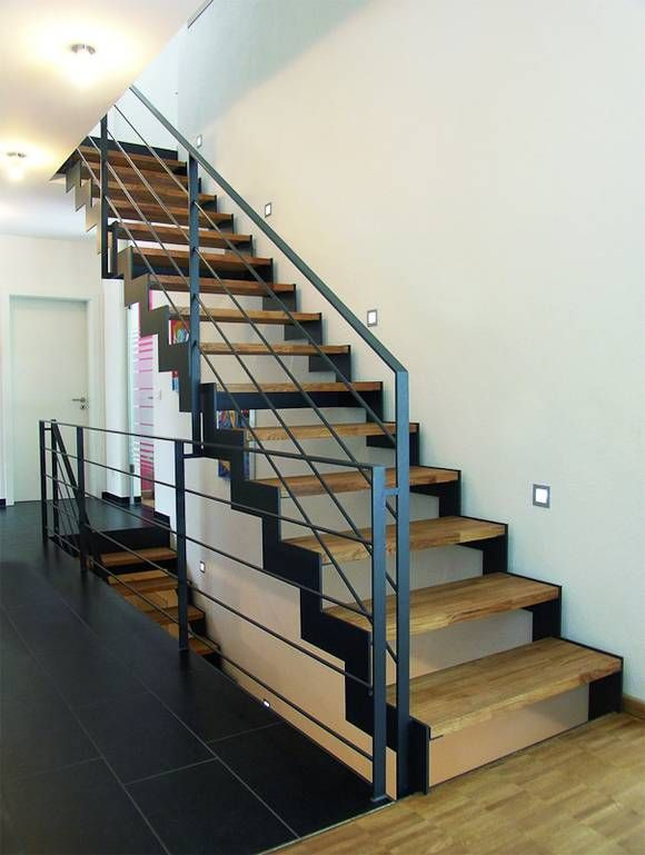 Modern wirkt dieses Treppenhaus, dank der Kombination aus hellem Holz, schwarzen Fliesen und schwarzem Eisengeländer.