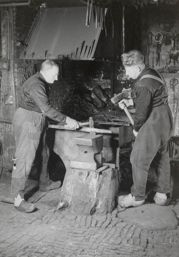 ader en zoon Kooiker aan het werk in hun smederij te Rouveen. Beiden zijn gekleed in streekdracht. 1944 #Overijssel #Staphorst