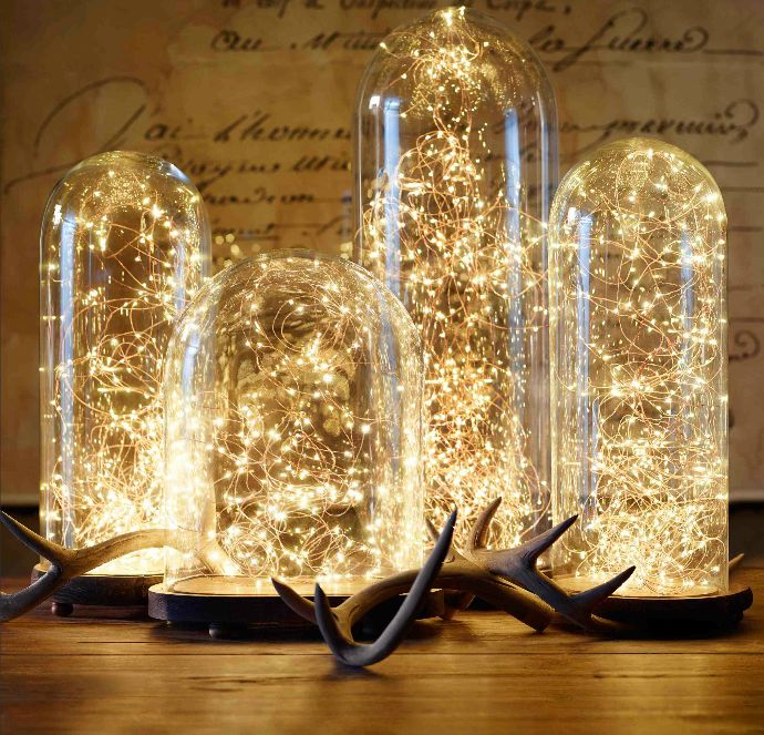 Battery powered twinkle lights in glass hurricanes or domes on mantel