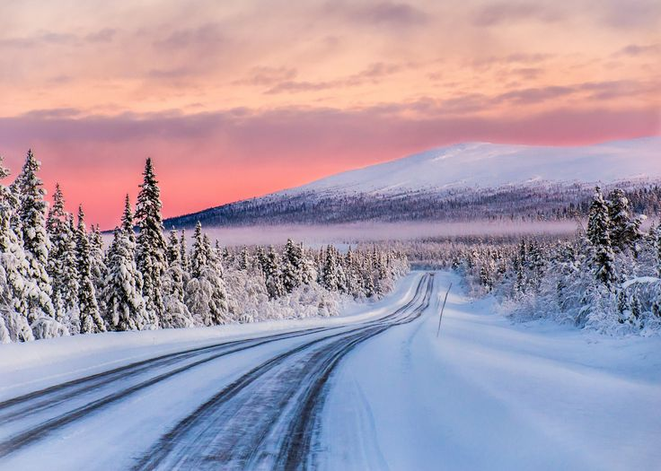Road to Dundret - Cold winter day (-28 C) above the Arctic Circle on an empty road outside Gällivare, Lapland, Sweden. The mountain Dundret in the background. At this time of the year you don´t see the sun, only the traces of it.