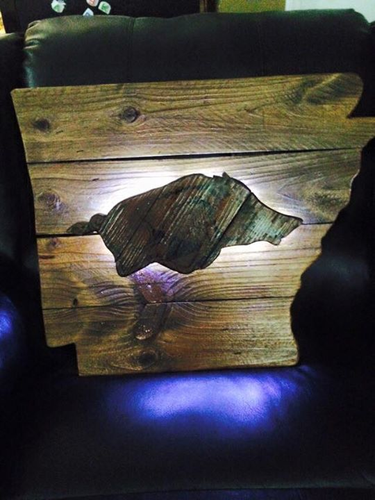 Arkansas Razorback on the state of Arkansas with lights behind the hog. Made from reclaimed wood