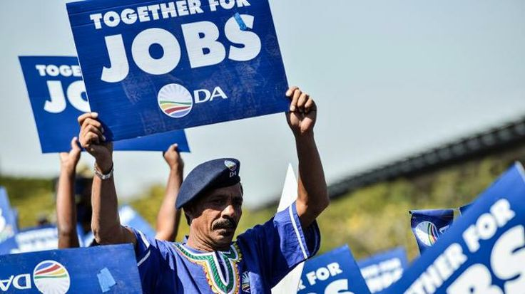Supporters of South Africa's main oppostion party Democratic Alliance (DA) wave placards asking for jobs as they gather at the Walter Sisulu Square in Kliptown, Soweto, to attend a concert on May 4, 2014.  AFP PHOTO / MUJAHID SAFODIEN