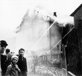 1938 Young onlookers watch as the local fire department prevents the fire from spreading to nearby houses, but makes no attempt to stop the synagogue from burning.